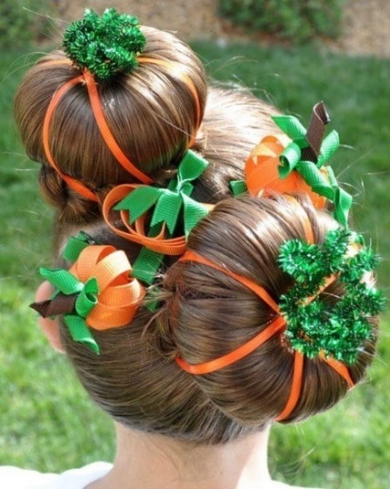 back view of a woman with hair buns decorated into pumpkins with ribbons