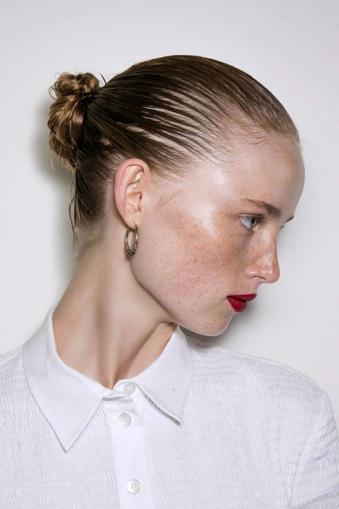 Easy updos - side view of a model with a wet look bun and red lipstick