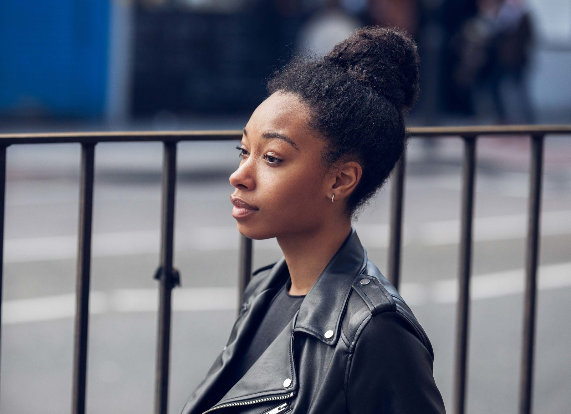 Curly hair hairstyles: Side profile of a black woman with natural hair styled in a high bun in street style picture wearing a black leather jacket.