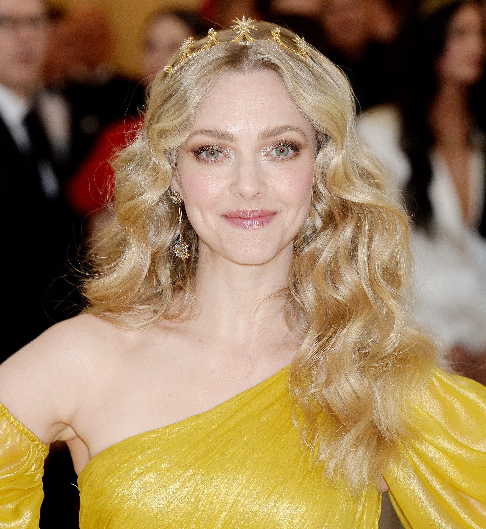 Curly hair hairstyles: Amanda Seyfried long golden blonde naturally curly hair with gold tiara headband wearing a one shoulder yellow dress