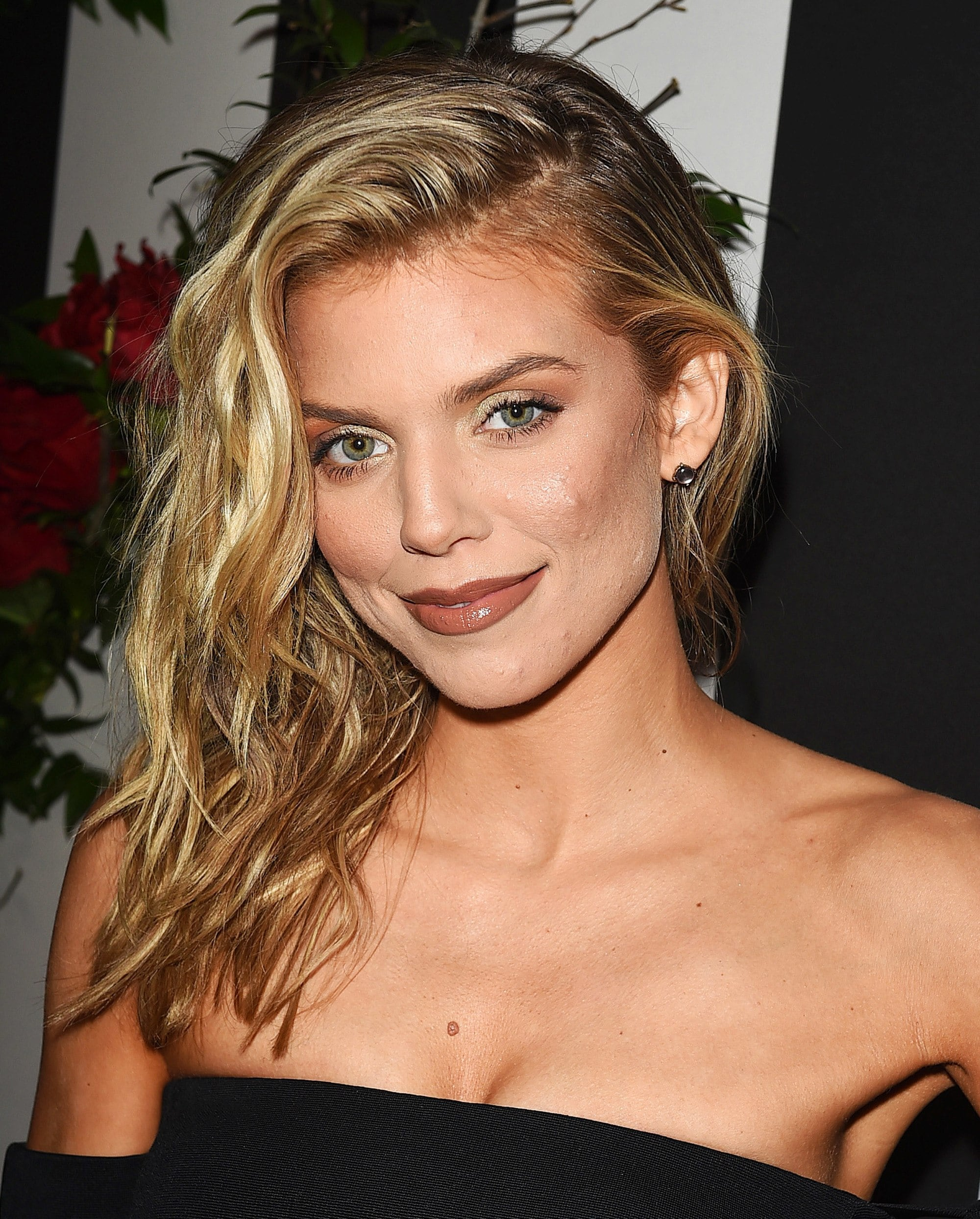Curly hair hairstyles: AnnaLynne McCord tousled golden blonde wavy hair swept across one shoulder wearing a strapless black dress