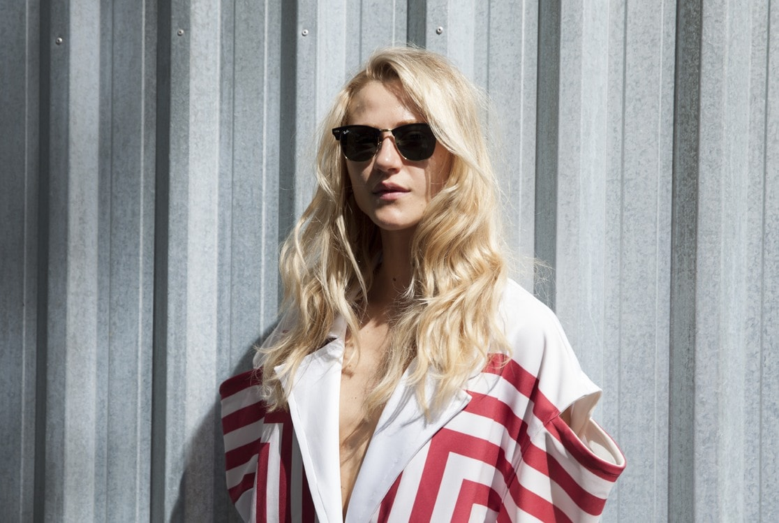 natural wavy hair: close up shot of woman with beachy waves, wearing printed outfit with sunglasses, posing against a backdrop