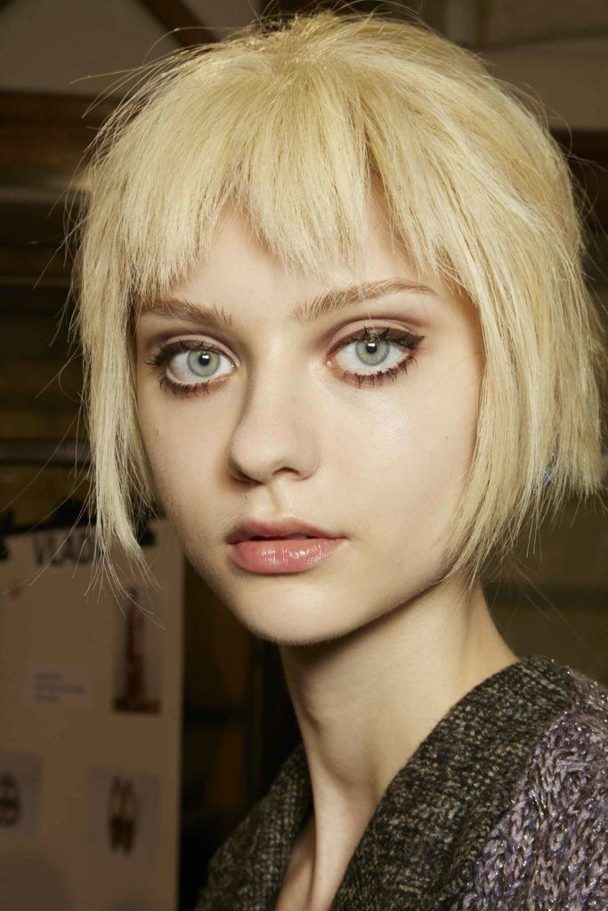 close up shot of a model with flaxen blonde hair cut into a choppy bob and fringe