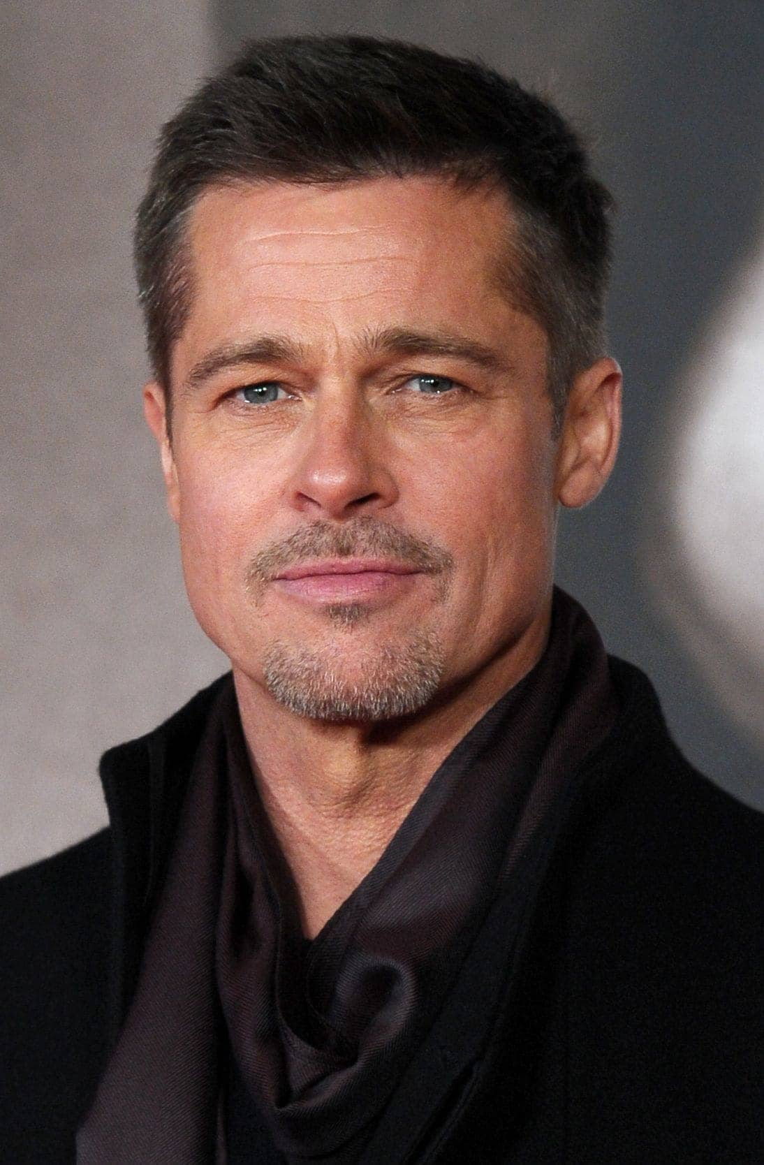 close up shot of brad pitt with crew cut hairstyle, wearing black top and posing