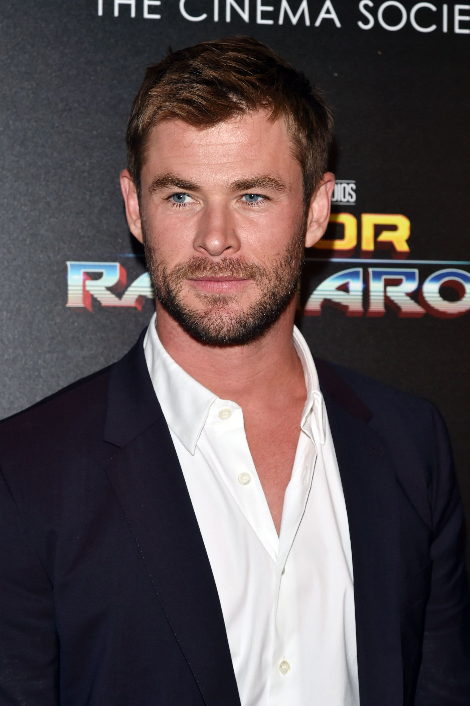 close up picture of Chris Hemsworth with swept back hairstyle on the red carpet, wearing white shirt and suit jacket