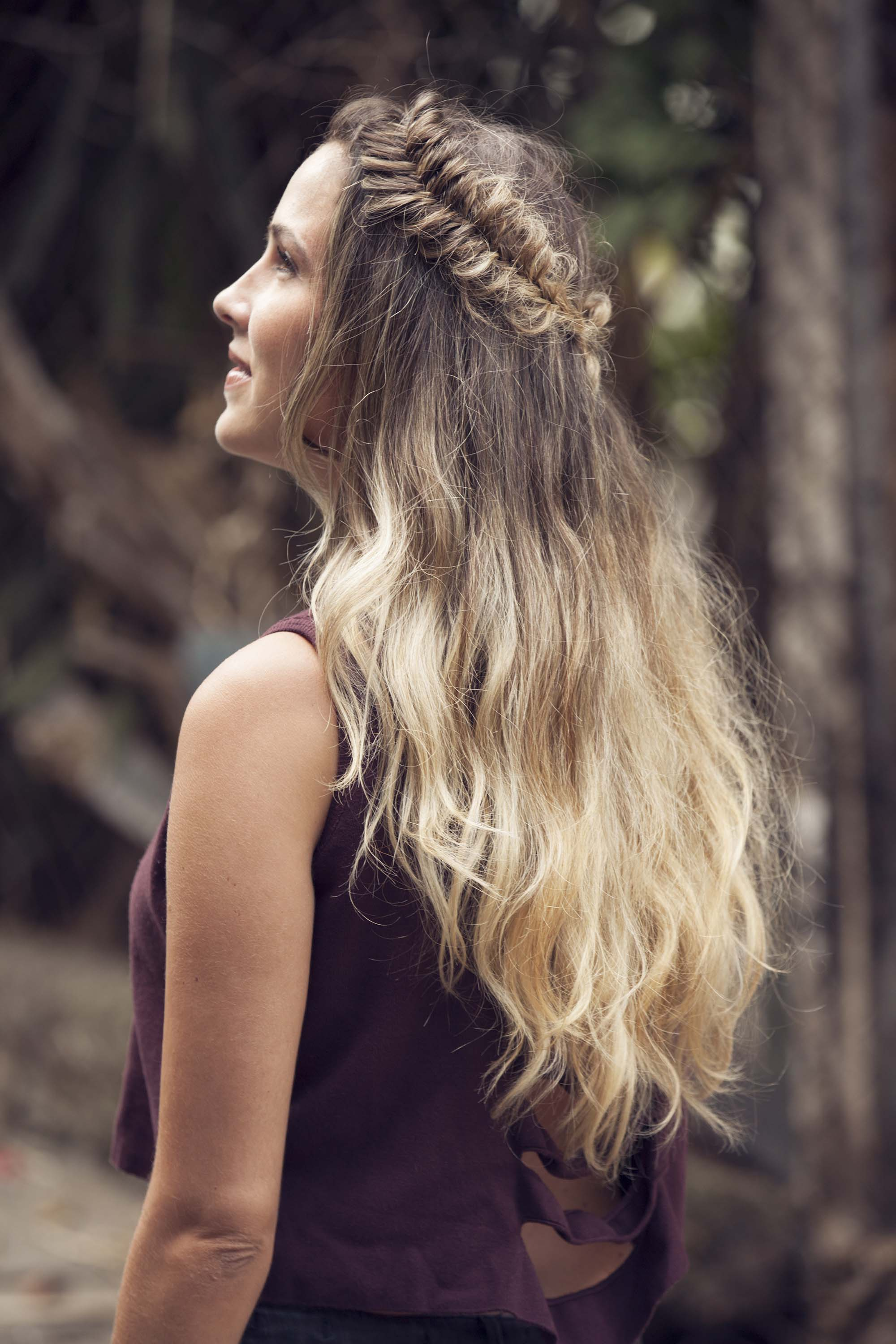 Fishtail braids: Woman with long ombre brown and blonde wavy hair styled with a fishtail crown braid