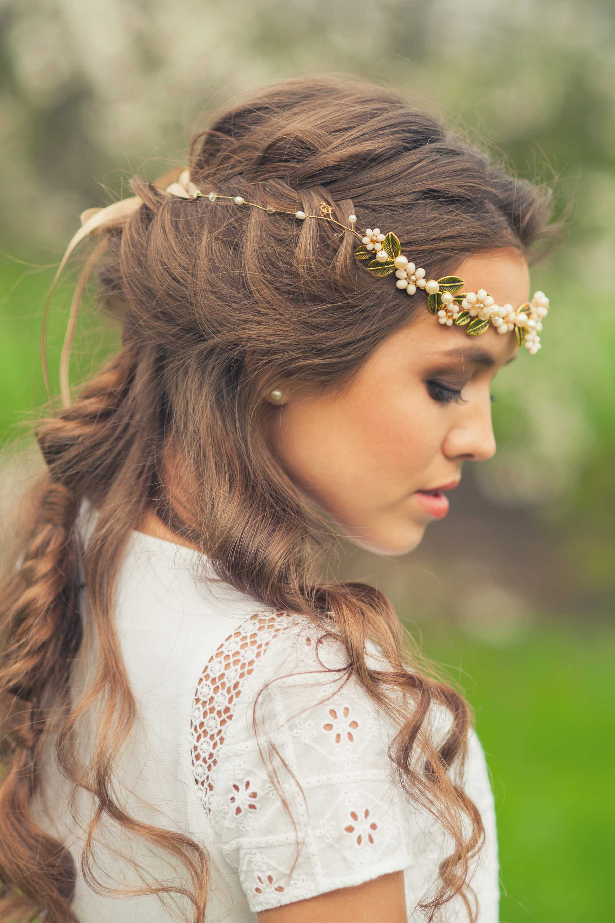 Curly wedding hair: Side view of a woman with medium brown hair worn in curls and braids with a flower crown accessory