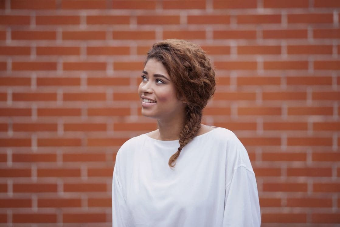 Woman with golden brown naturally curly hair styled in a side fishtail braid wearing a white top standing against a wall backdrop.