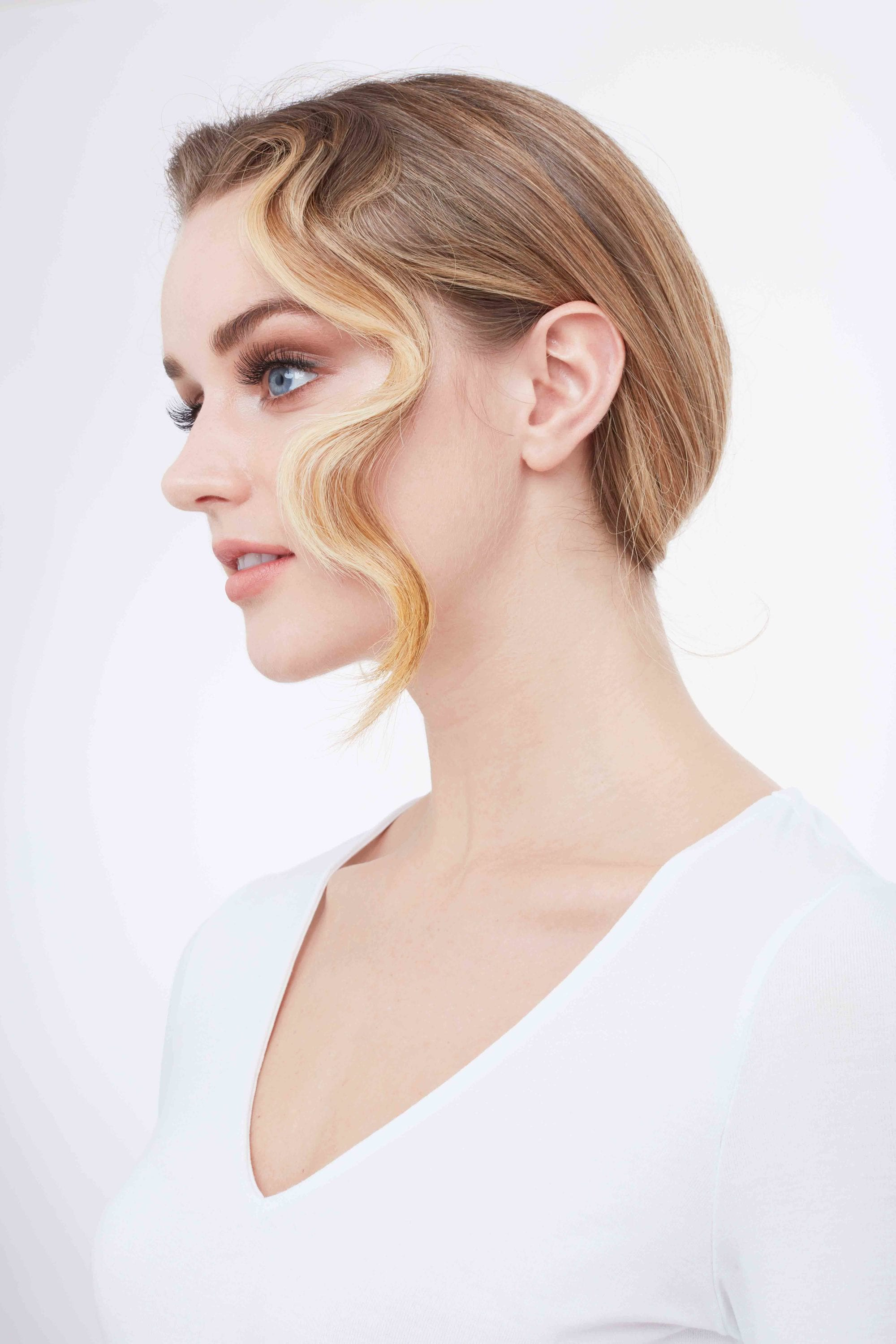 How to curl your hair: Blonde woman with her hair in an updo with a single 1920s style s-shaped wave, wearing a white v-neck t-shirt