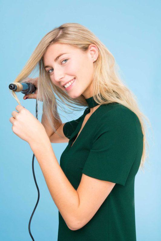 a woman iron curling her blonde hair