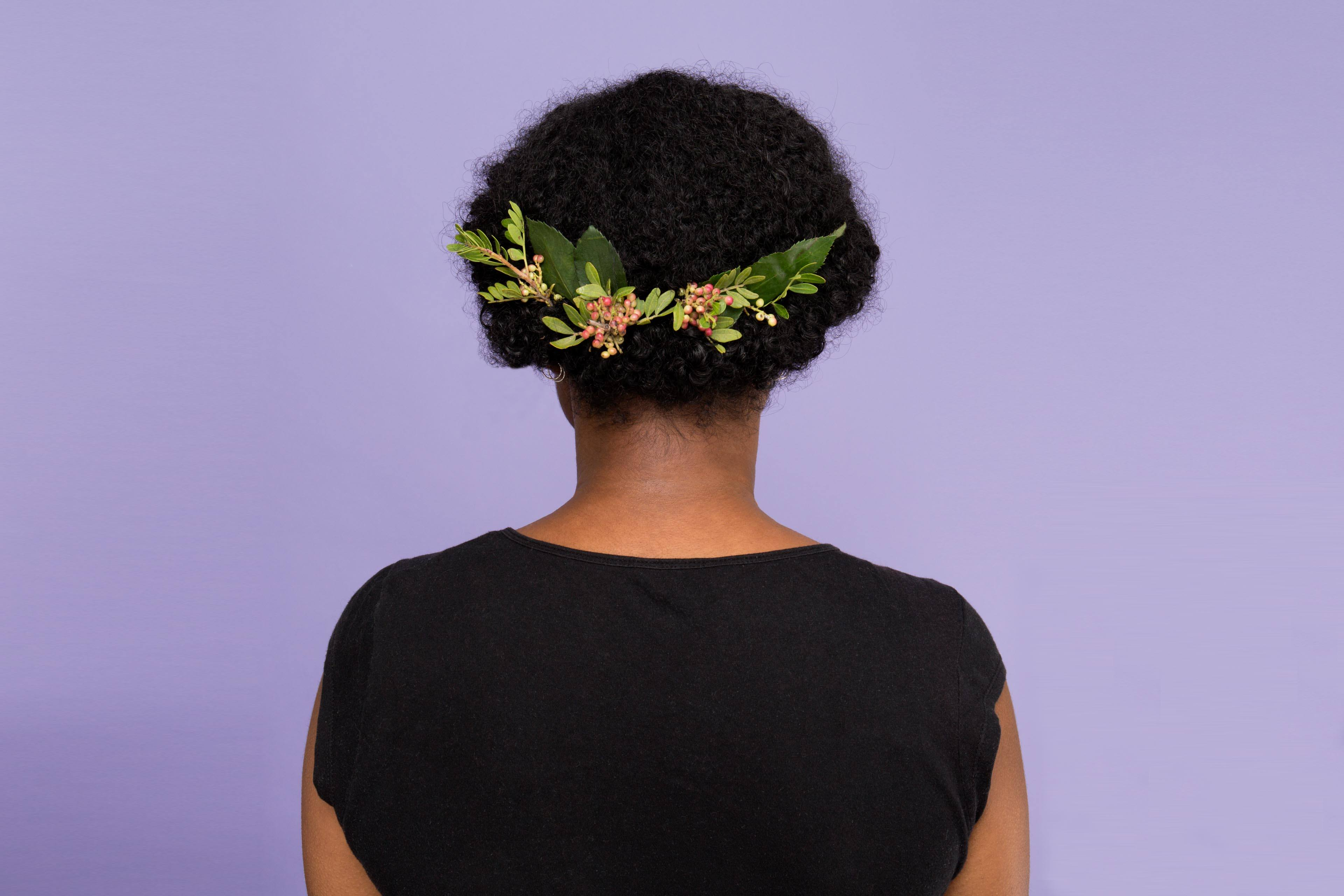 Curly wedding hair: Back view of a woman with her dark afro hair worn in a chignon bun with a floral hair accessory attached