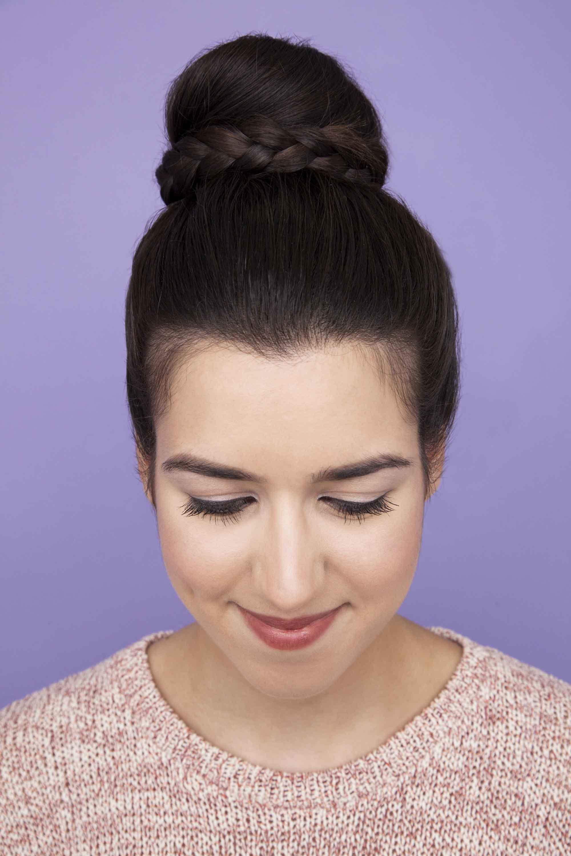 Easy braid hairstyles: Brunette girl with braided ballerina bun looking down