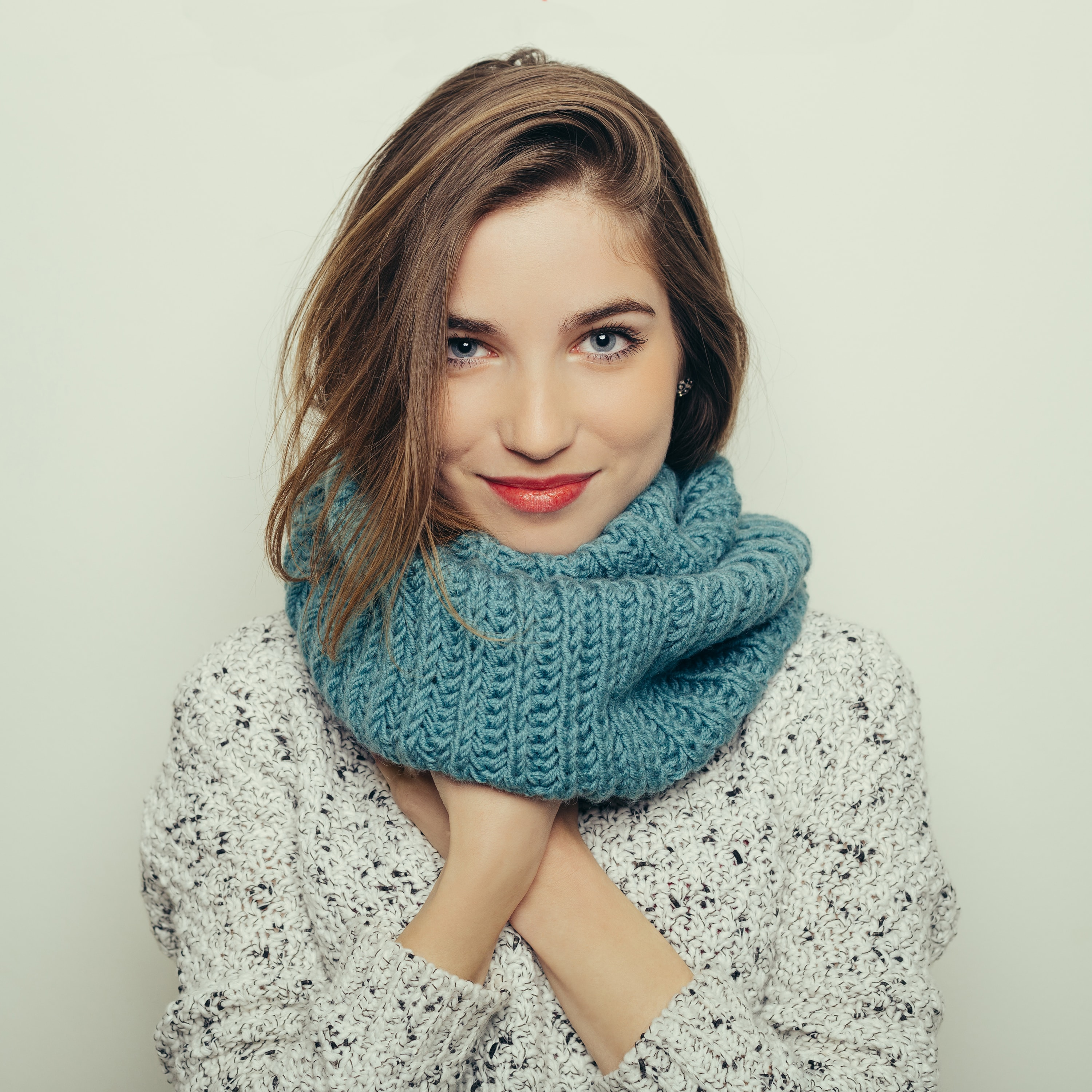 Hair mask: Shot of a young woman with chocolate brown hair, wearing a blue scarf and floral print top in a studio