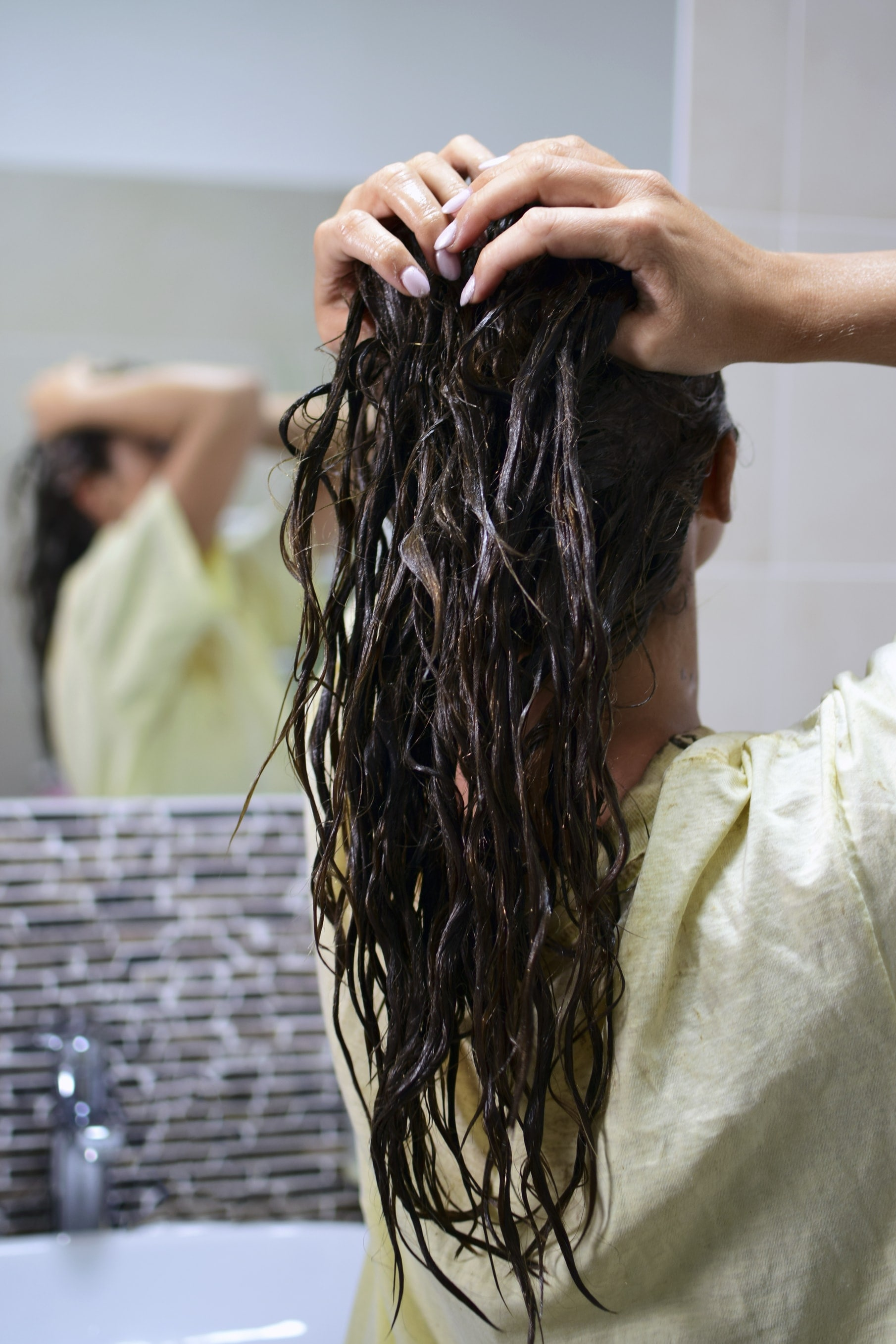 Hair mask recipe: Back shot of young woman with wet dark brown curly hair with a deep conditioner in it, posing in a bathroom