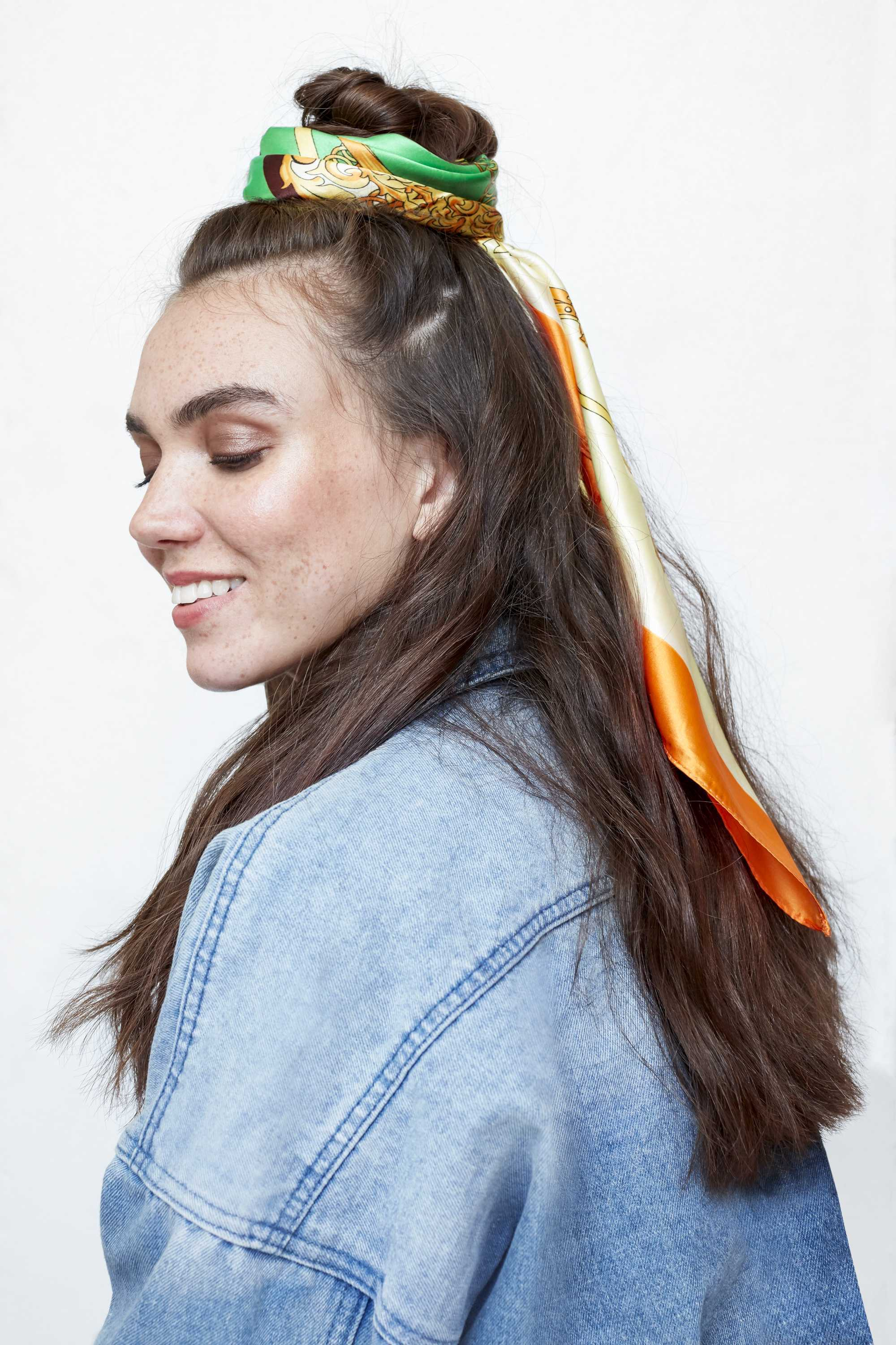 freckled brunette model with her long dark wavy hair in a half up half down bun with a green and orange headscarf tied around the bun wearing a denim jacket