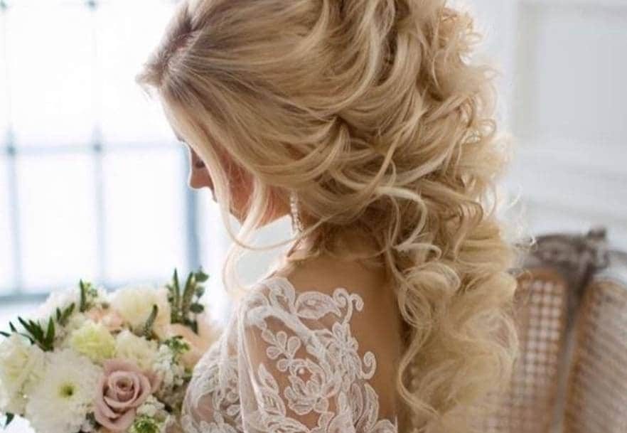 Curly wedding hair: Woman with light blonde hair long curls half up with flowers