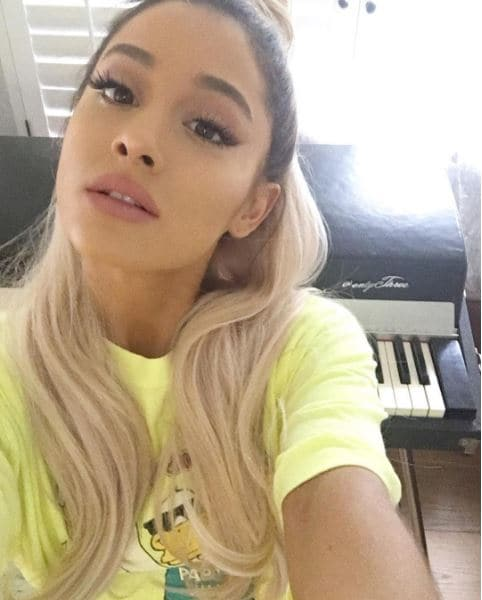 Ariana Grande taking a selfie wearing a yellow t-shirt with blonde hair and dark roots worn long and over her shoulder