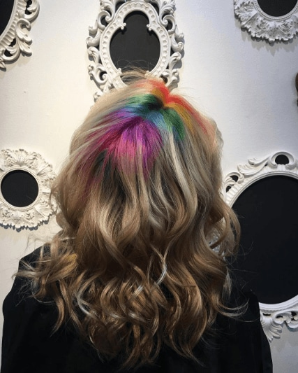 woman with wavy brown hair and rainbow roots