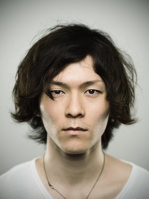 front shot of an asian man with a medium length messy shag haircut