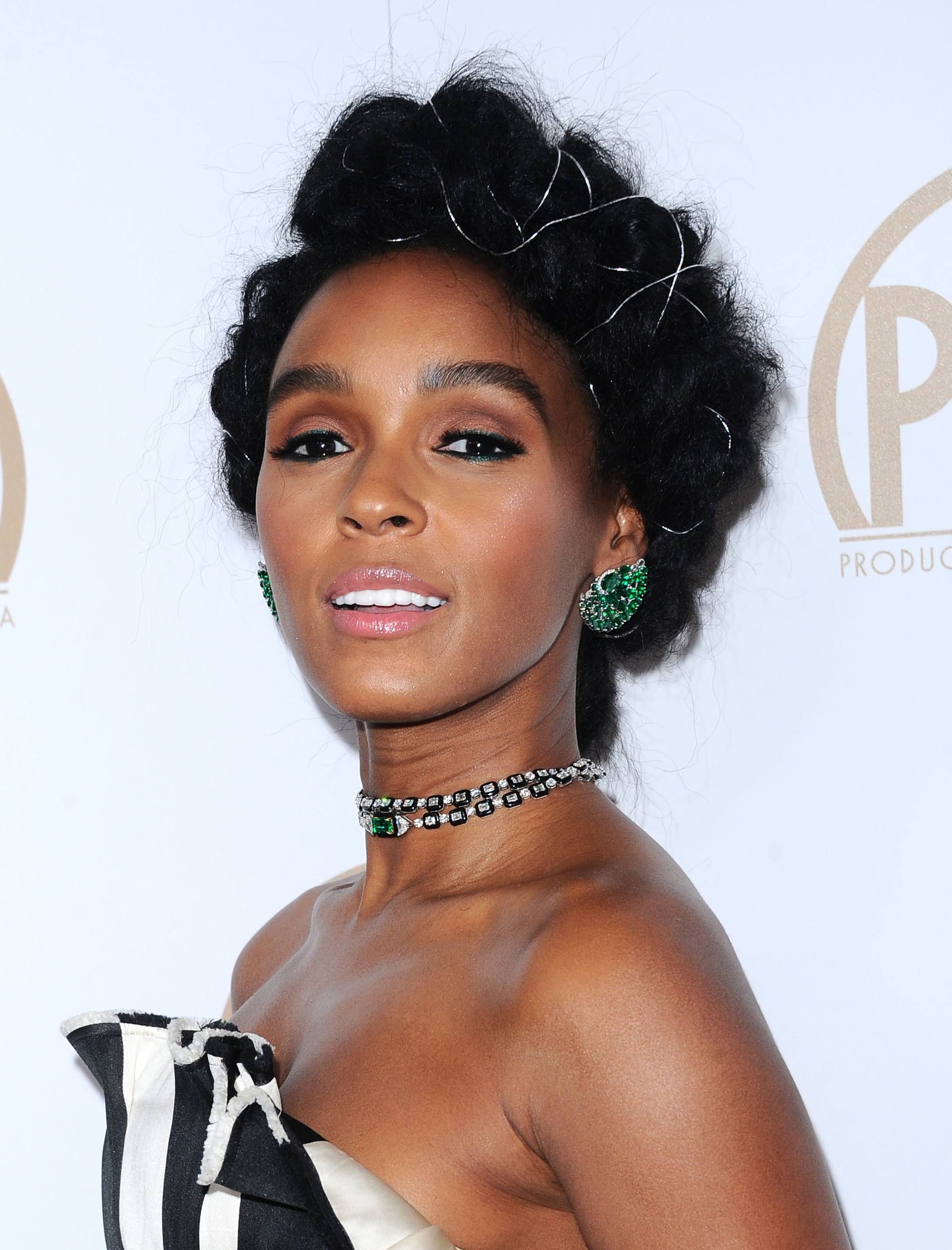 Curly hair hairstyles: Janelle Monae natural hair in halo braid updo on the red carpet wearing a strapless black and white dress