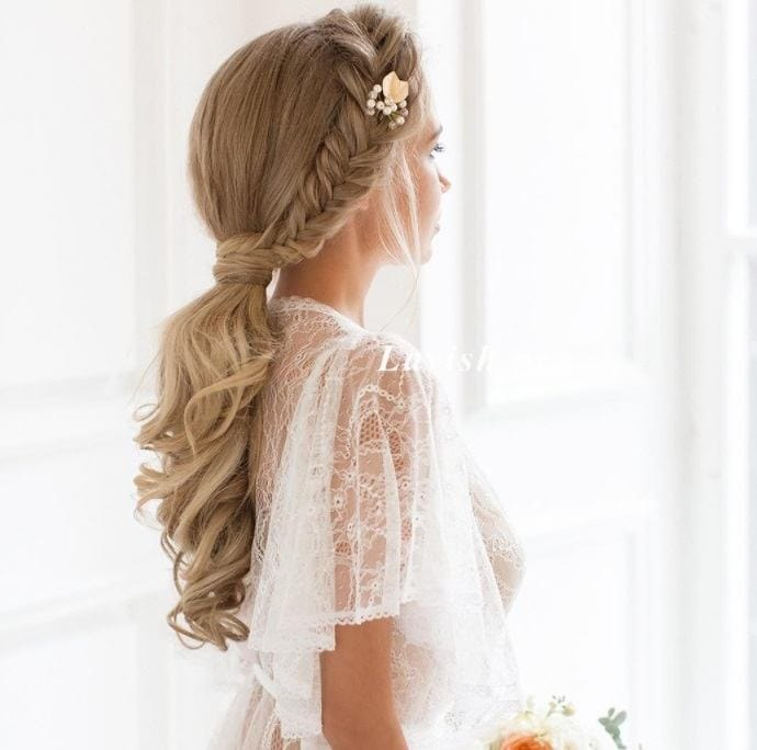 Curly wedding hair: Back view of a bride with long blonde hair worn in curls and a side braid ponytail