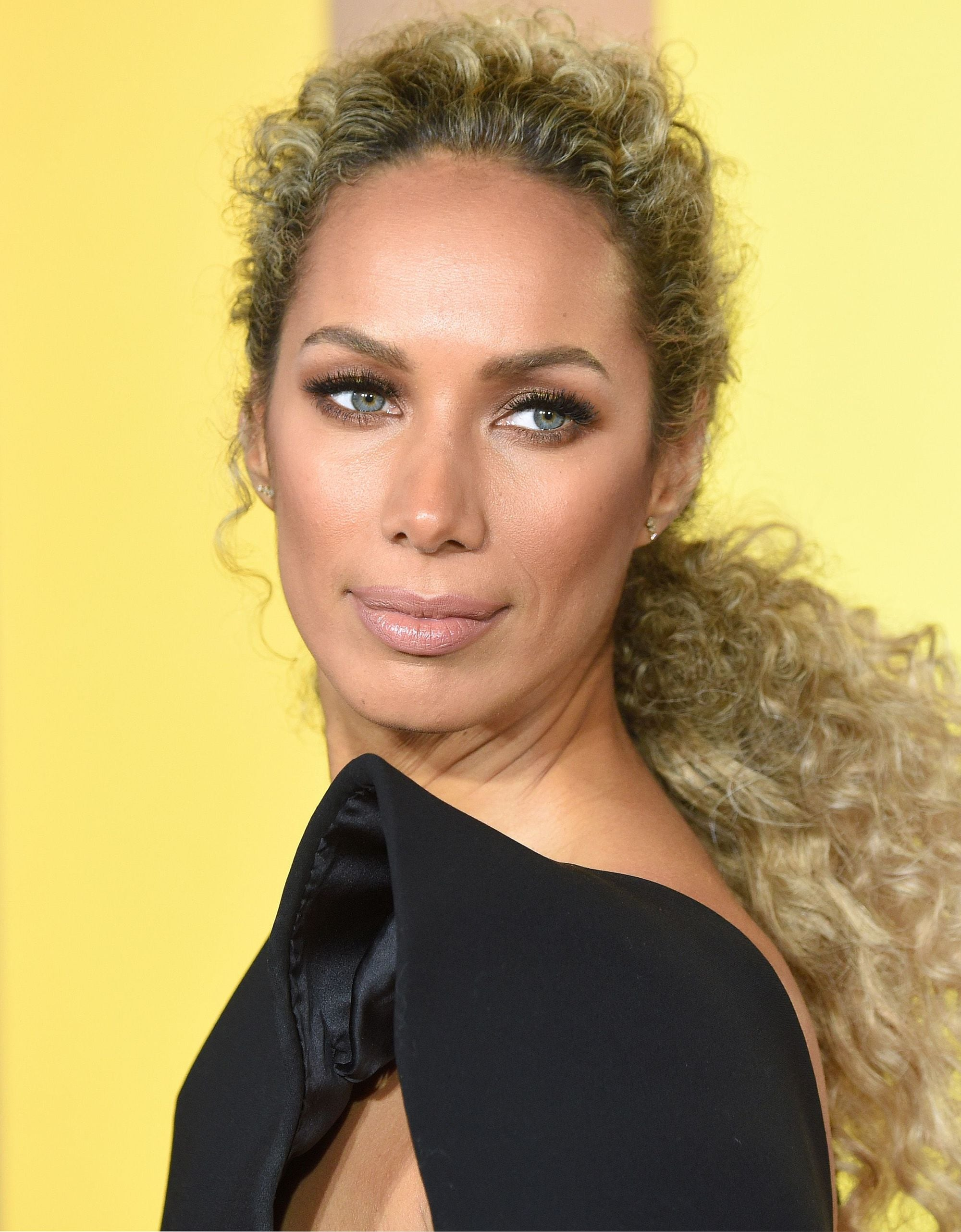Curly hair hairstyles: Leona Lewis with long golden blonde bronde naturally curly hair styled in a textured low ponytail standing against a yellow backdrop at the Black Panther premiere in London