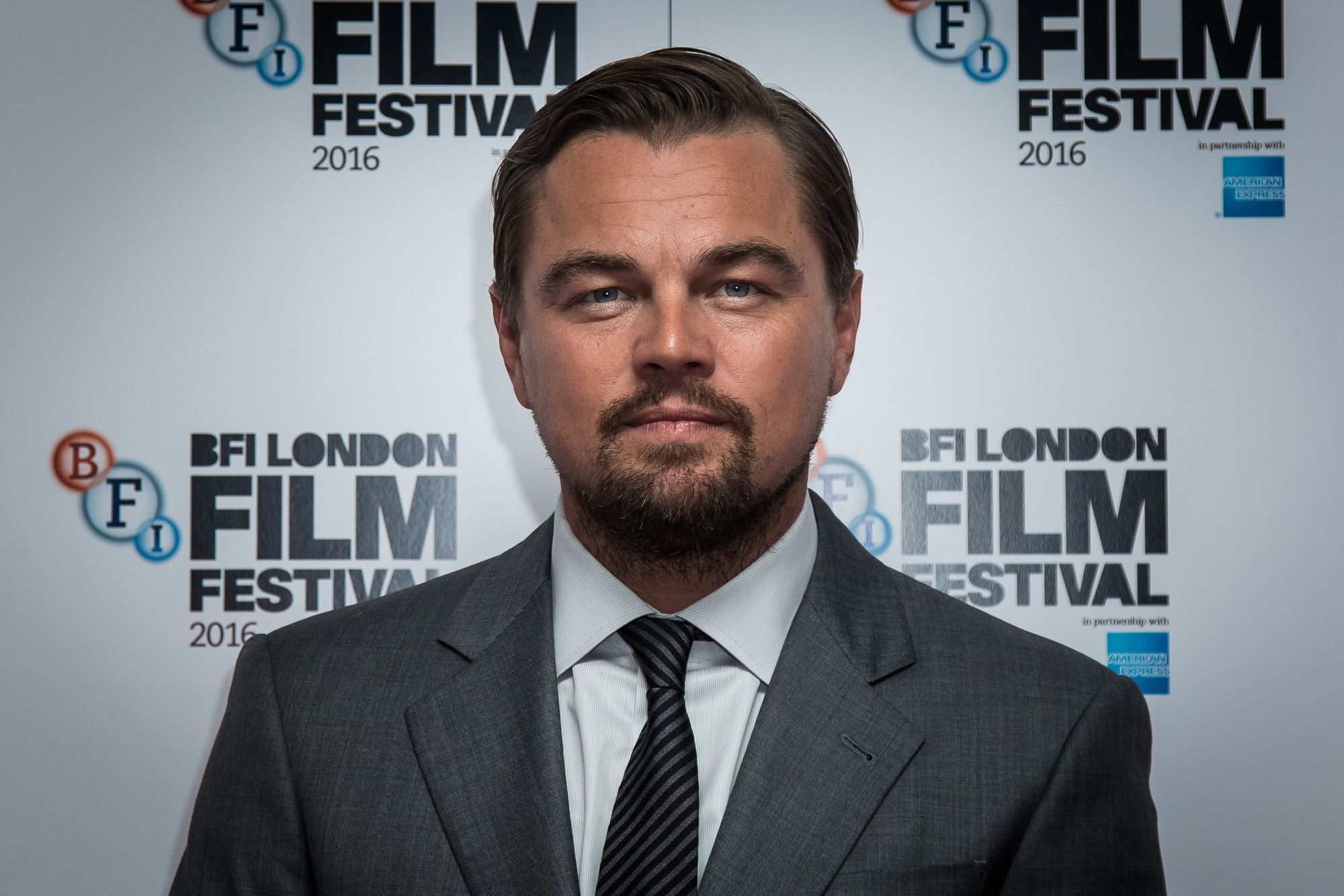 close up shot of leonardo dicaprio on the red carpet with side part hairstyle, wearing suit and tie