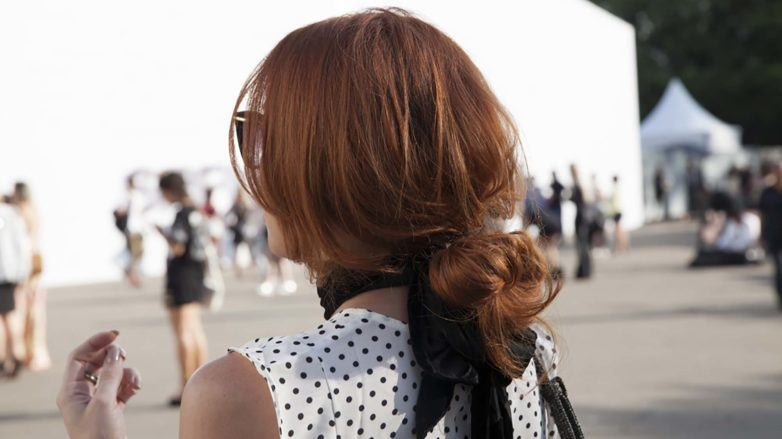 Updos for long hair: Model with brown hair in low messy bun hairstyle with a large black bow ribbon and spotted top
