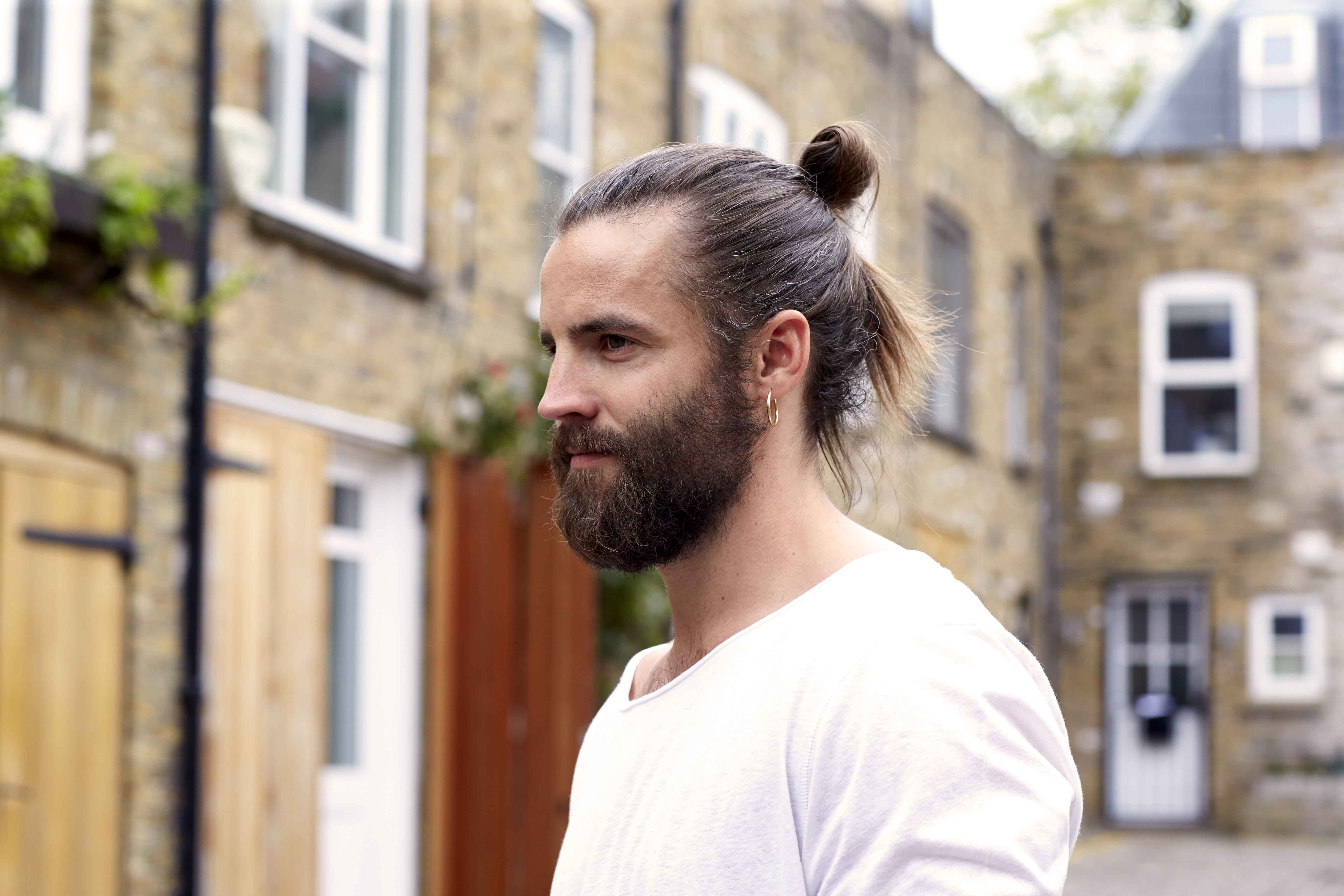 brunette bearded man with a man bun hairstyle
