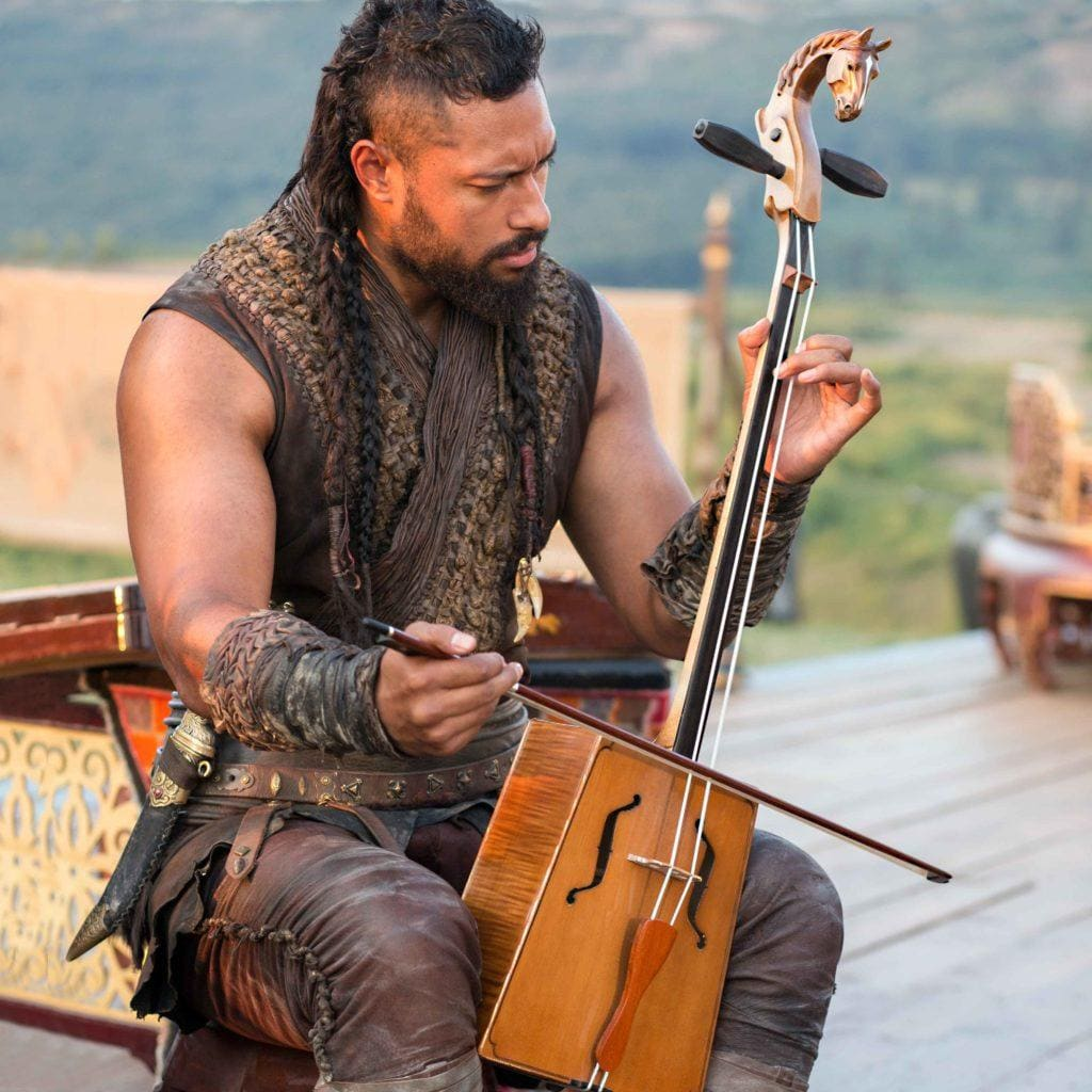 Man with long dark hair worn in an undercut with braids playing a musical instrument