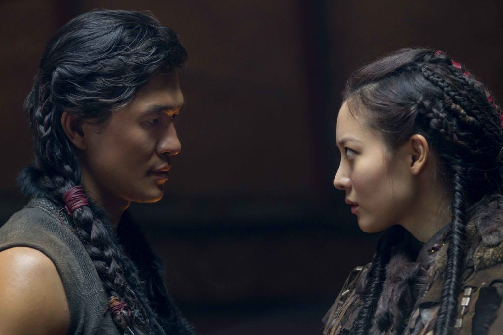 a side view of a man and a woman both with dark hair and the man wearing braids