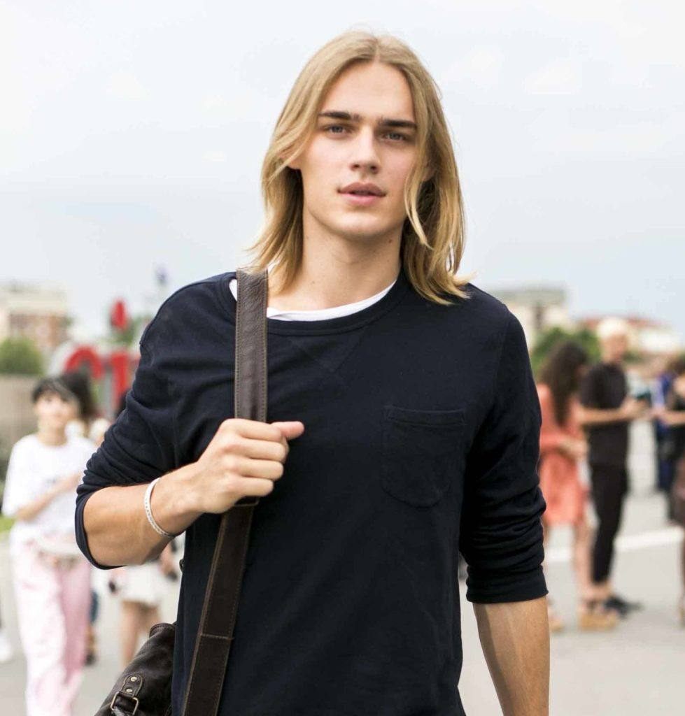 man with medium length blonde hair worn loose wearing a black tee shirt and denim shorts