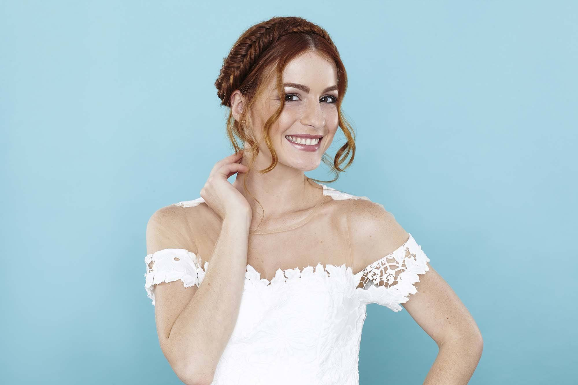 A young redhead woman wearing a white dress and with a fishtail milkmaid braid