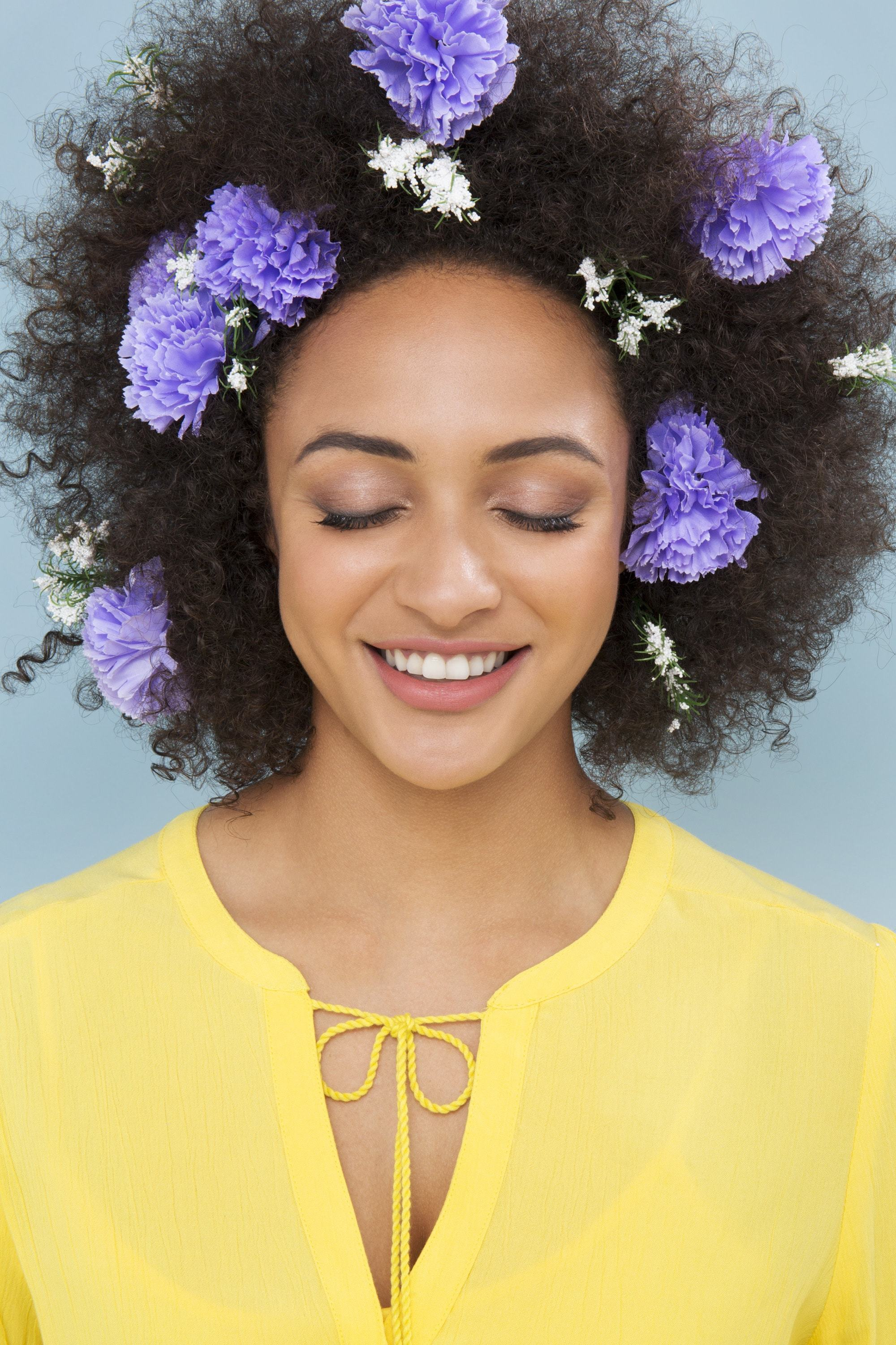 Curly wedding hair: Model with afro hair with flowers in it