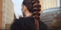 Pull through braid brunette girl standing outside with her back to camera