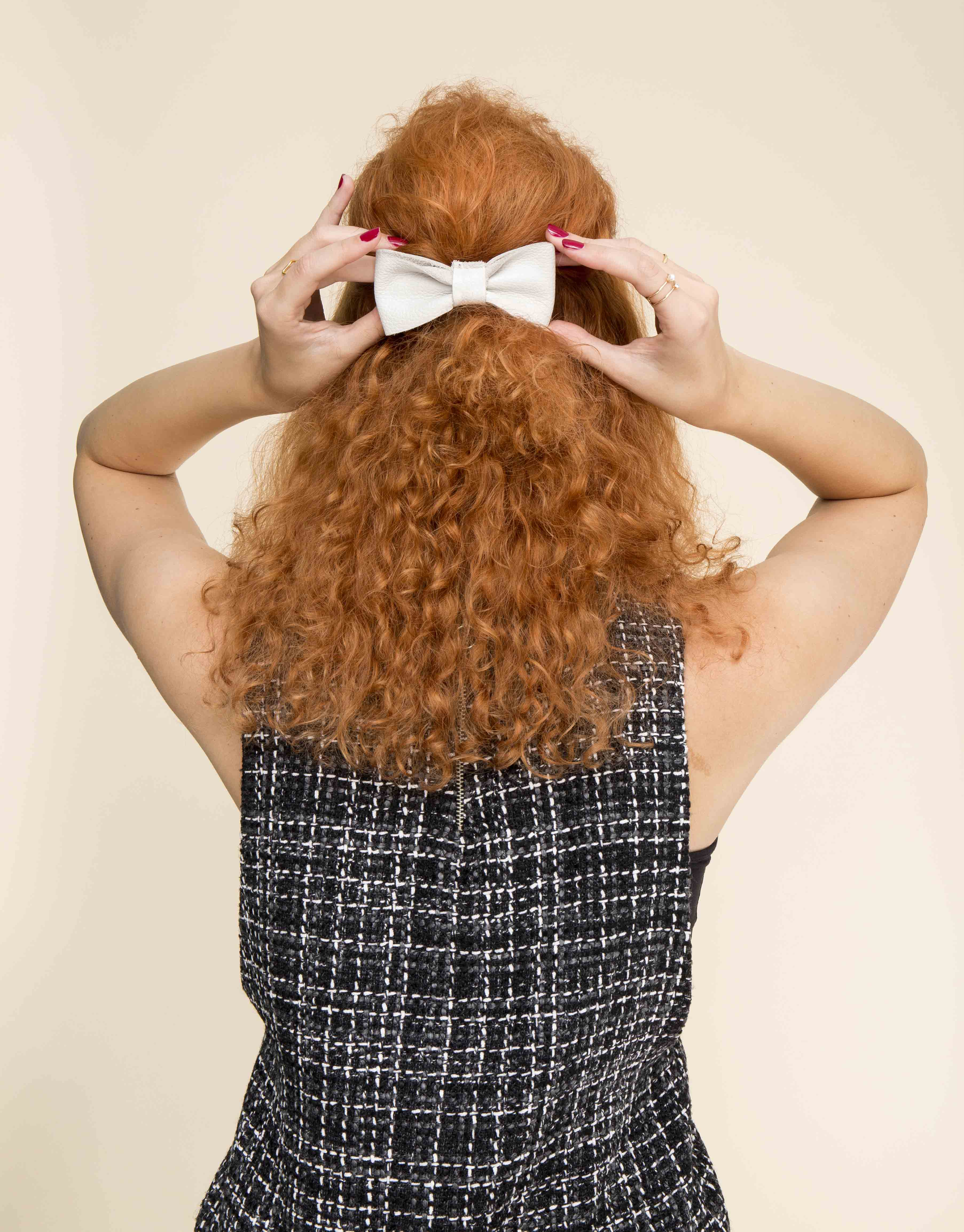 Curly wedding hair: Back view of a woman with ginger curly hair worn in a half up hairstyle with a white bow accessory attached