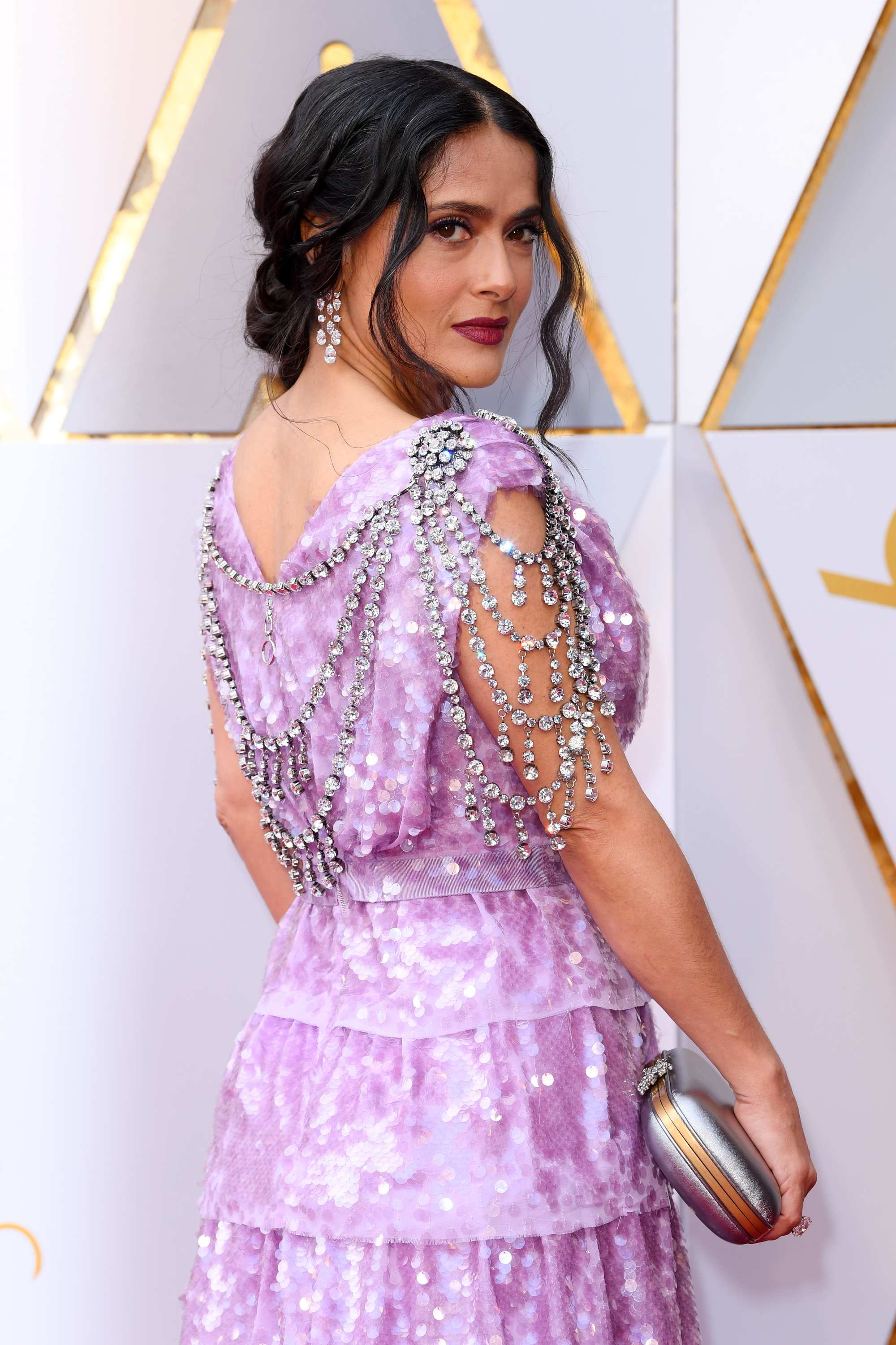 Curly hair hairstyles: Salma Hayek dark brown hair in romantic and ethereal updo on the red carpet wearing a light purple dress