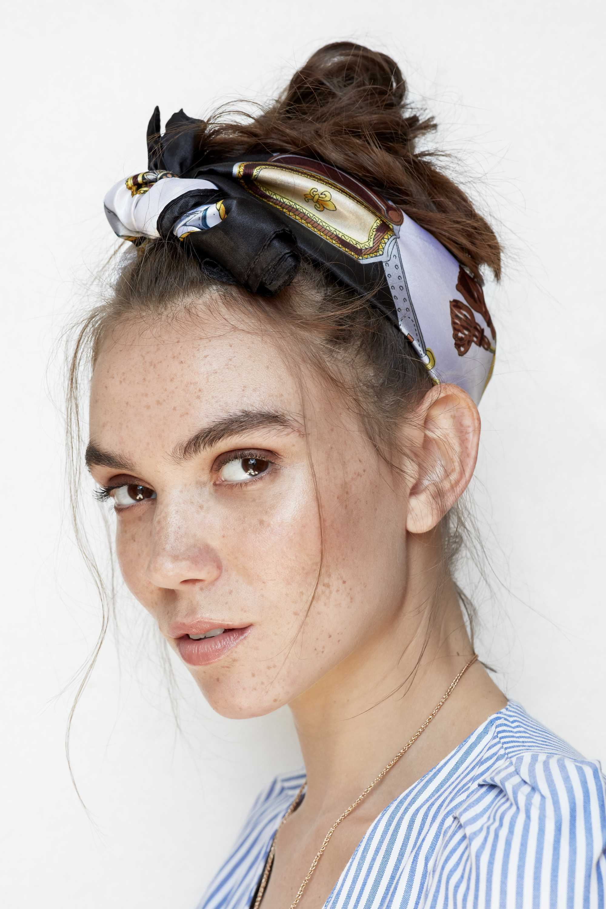close up head shot of a freckled brunette model with her hair in a messy bun updo with a printed blue and gold scarf wrapped around it tied in a bow