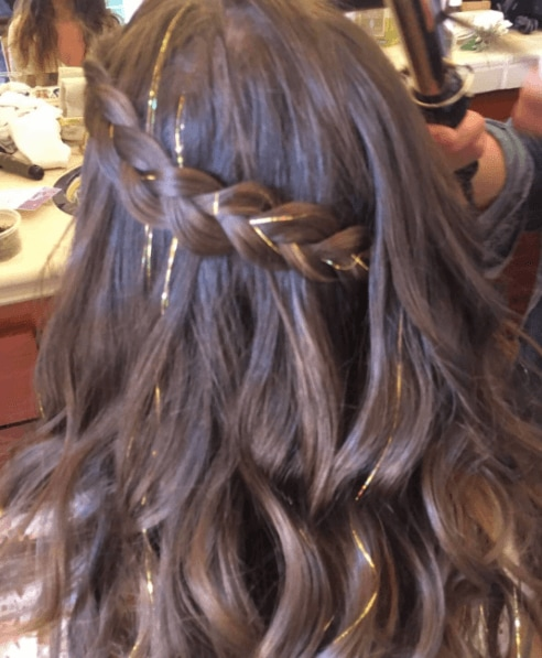 back of a woman's head with brown hair in a braid with gold tinsel hair