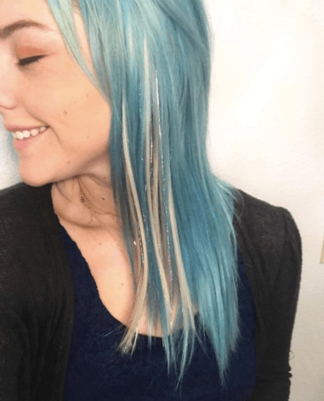 side view of a woman's face with blue hair and tinsel streaks