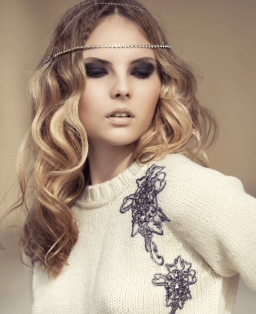 Christmas hairstyles: Woman with medium length blonde wavy hair styled with a headband wearing a cream knitted jumper.