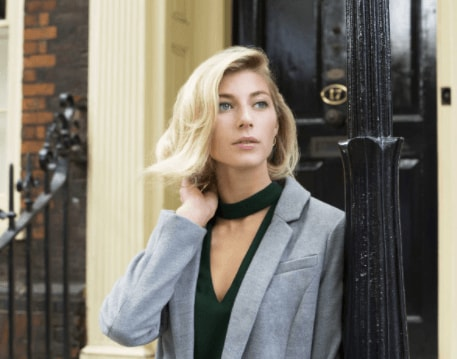 Christmas hairstyles: Blonde woman with hair styled in a flipped out bob wearing a grey blazer over a black top touching her hair.