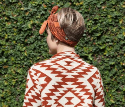 Christmas hairstyles: woman with short straight blonde hair wrapped with a headband bandana wearing a red and white aztec top.