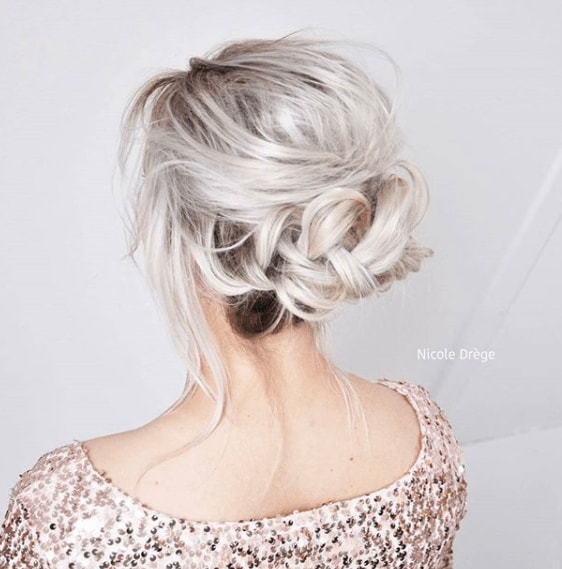 Fishtail braids: Woman with white blonde hair in fishtail bun updo.