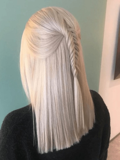 Fishtail braids: Woman with her blonde hair half up with a fishtail hairstyle