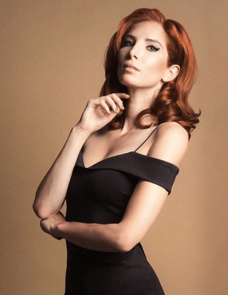 front view of a woman in a black dress with red hair