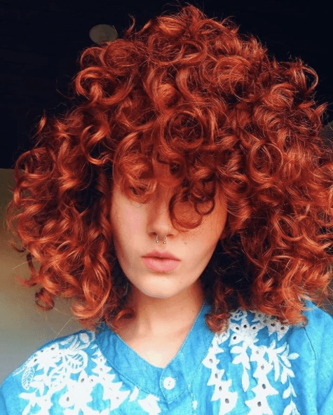 front view image of a woman with red curly hair