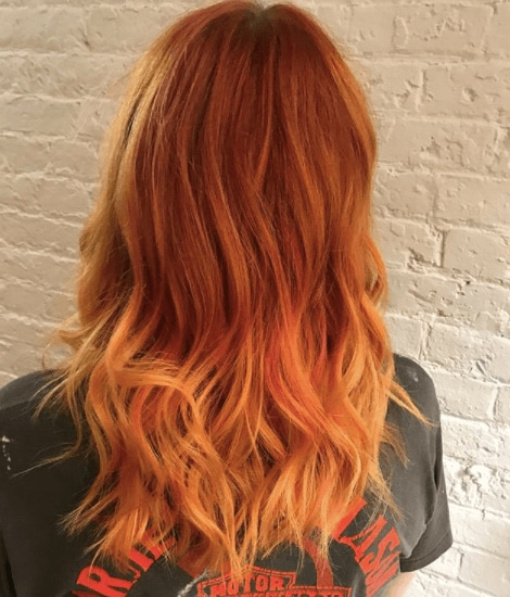 back view of a woman with bright red hair colour and orange ends