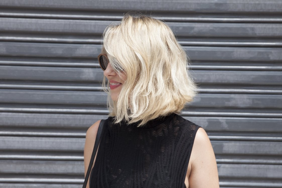 natural wavy hair: street style shot of woman with tousled blonde bob, wearing a black top with a matching handbag, posing against a backdrop