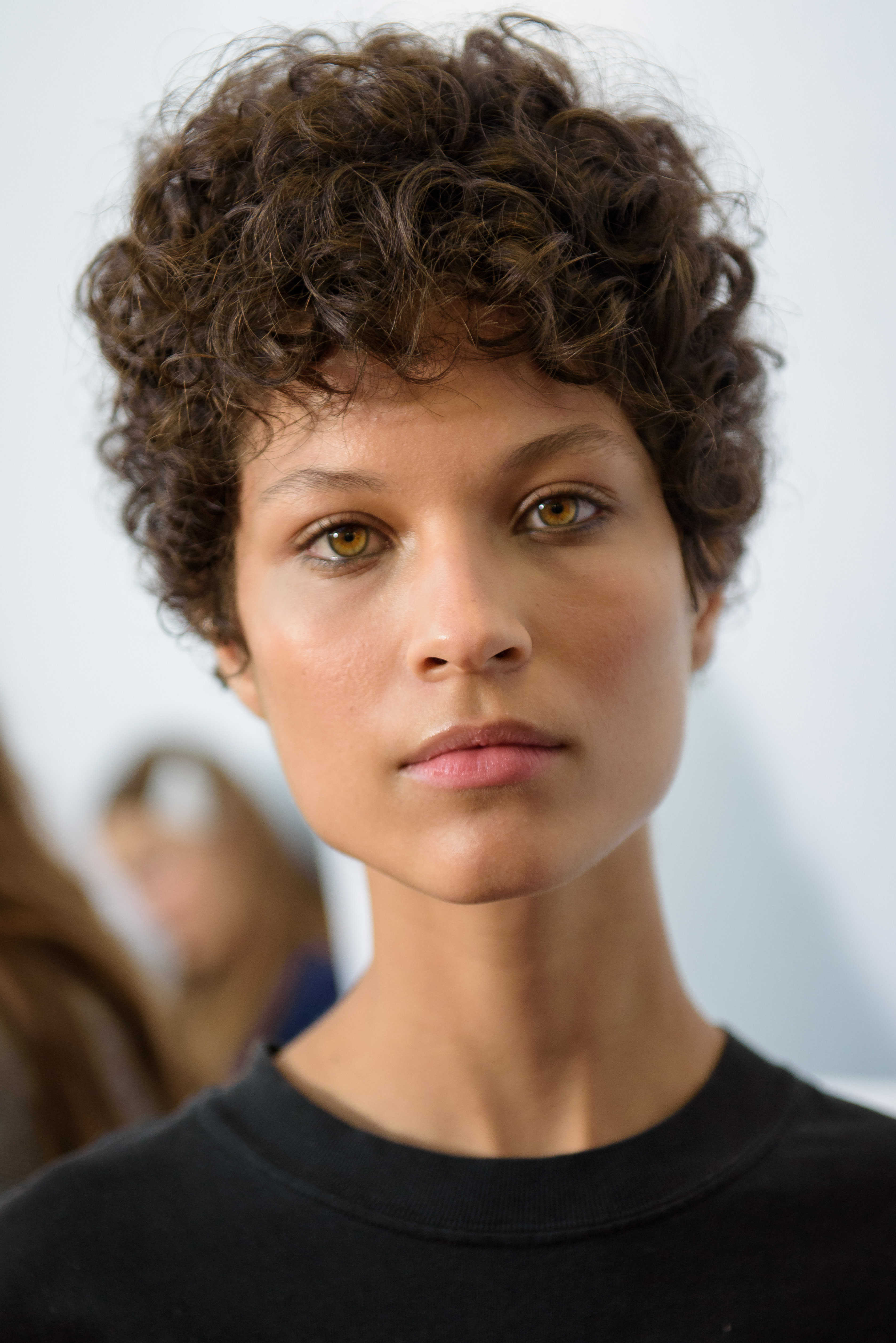 Short hairstyles for curly hair: Woman with pixie cut light brown curls